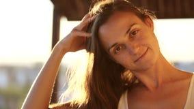 Ung nätt kvinna som ler och ser kameran på balkongen på solnedgången arkivfilmer