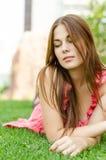 Ung nätt kvinna som ligger på grönt gräs i park Royaltyfri Foto