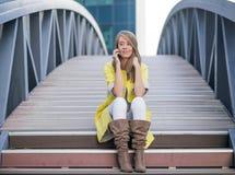 Ung nätt kvinna som talar på mobiltelefonen på bron - kvinna som har en konversation på smartphonen Royaltyfri Fotografi
