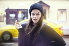 Ung nätt kvinna som utanför röker Hipsterdräkt, bärande svart hatt och t-skjorta, gul taxi för stad på bakgrunden Arkivbild