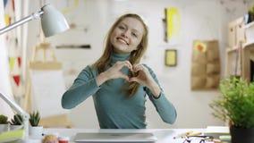 Ung nätt kvinna som visar en hjärta som göras av fingrar till kameran lager videofilmer