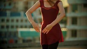 Ung nätt kvinnaballerina i det röda klänninganseendet på taket - dans med hennes händer - ljus solnedgång lager videofilmer