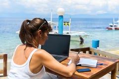 Ung nätt kvinnafreelancerförfattare som framme arbetar med den bärbar datornotepaden och telefonen av det blåa tropiska havet royaltyfri foto
