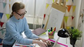 Ung nätt kvinnlig student som gör läxa vid bärbara datorn arkivfilmer