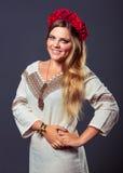 Ung nätt le flicka i ukrainsk dräkt med en röd krans Royaltyfri Bild