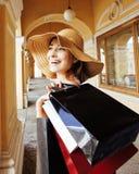 Ung nätt le kvinna i hatt med påsar på shopping på lagret arkivbild