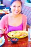 Ung nätt lycklig kvinna för blandat lopp som äter Chimichanga arkivfoton