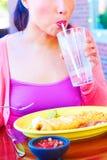 Ung nätt lycklig kvinna för blandat lopp som äter Chimichanga royaltyfria bilder
