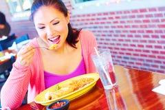 Ung nätt lycklig kvinna för blandat lopp som äter Chimichanga arkivfoto