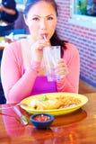 Ung nätt lycklig kvinna för blandat lopp som äter Chimichanga royaltyfria foton