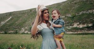 Ung nätt moder som spelar med hennes barn i mitt av landskapet som ler lager videofilmer