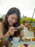 Ung nätt och lycklig asiatisk koreansk loppbloggerkvinna som tar bilden med mobiltelefonen av den härliga frukosttabellen på utom arkivfoto