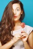 Ung n?tt brunettkvinna som poserar lyckligt gladlynt p? bl? bakgrund med godisen, livsstilfolkbegrepp arkivbild