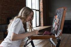 Ung n?tt flicka med borsten och palett som sitter n?ra staffliteckningsbild Konst kreativitet, hobby som drar process royaltyfri fotografi