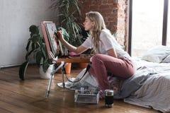 Ung n?tt flicka med borsten och palett som sitter n?ra staffliteckningsbild Konst kreativitet, hobby som drar process arkivfoton
