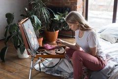 Ung n?tt flicka med borsten och palett som sitter n?ra staffliteckningsbild Konst kreativitet, hobby som drar process royaltyfria bilder