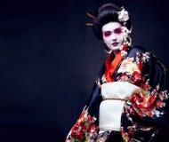 Ung n?tt geisha i kimono med sakura och garnering arkivbilder