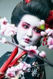 Ung n?tt geisha i svart kimono bland sakura, asiatisk ethnocloseup royaltyfria bilder