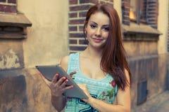 Ung nätt flicka som gör on-line shopping genom att använda minnestavlan Royaltyfri Bild