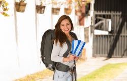 Ung nätt kvinna som bär tillfälliga kläder och ryggsäcken som framme står av kameran och att le lyckligt som rymmer lopp Fotografering för Bildbyråer