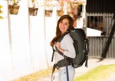 Ung nätt kvinna som bär tillfälliga kläder och ryggsäcken som framme står av kameran som lyckligt ler, fotvandrarebegrepp Arkivfoto