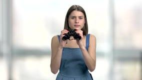 Ung nyfiken kvinna med kikare stock video