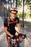 Ung och driftig cyklist i parkera Arkivfoto