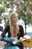 Ung och gullig blond flicka på en motorisk sparkcykel Arkivfoton