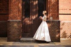Ung och härlig brud i det vita bröllopsklänninganseendet nära trädörren arkivbild