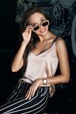 Ung och härlig flicka i en beige t-skjorta och svarta bakstycken i ett vitt band Mode för kvinna` s Stads- livsföring Fotografering för Bildbyråer