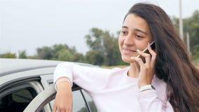 Ung och härlig flicka som talar på telefonen nära bilen Trevligt leende på framsida Närbild långsam rörelse stock video