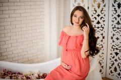 Ung och härlig gravid kvinna i en lång klänning arkivbilder