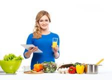 Ung och härlig hemmafrukvinnamatlagning i ett kök Arkivbilder