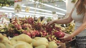 Ung och härlig kvinna i supermarket som köper ny och sund drakefrukt Pitahaya för familj Välja för arm stock video