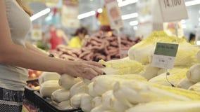Ung och härlig kvinna i supermarket som köper ny och sund kinakål och grönsaker för familj _ arkivfilmer
