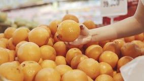 Ung och härlig kvinna i supermarket som köper nya och sunda apelsiner och frukter för familj Arm som väljer det smakligt stock video