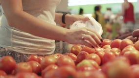 Ung och härlig kvinna i supermarket som köper nya och sunda tomater och grönsaker för familj Välja för arm arkivfilmer