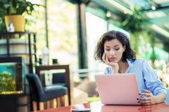 Ung och h?rlig flicka med anteckningsboken och b?rbara datorn som sitter i ett kaf? arkivbild