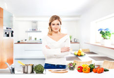 Ung och härlig hemmafrukvinnamatlagning i ett kök Arkivfoto