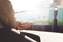 Ung och moderiktig stads- kvinna som använder smartphoneplanläggningstur i drevplattform i morgonen royaltyfri fotografi
