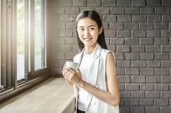Ung och nätt asia kvinna med kopp kaffeleende i kafé royaltyfri fotografi