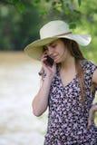 Ung och nätt kvinna som kallar med hennes smartphone royaltyfria foton