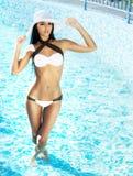 Ung och sexig kvinna i en baddräkt som poserar i simbassängen Royaltyfri Bild