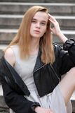 Ung och sexig redheaded flicka som utomhus poserar i läderomslag och kappa royaltyfri fotografi
