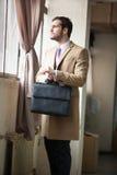 Ung och stilig affärsman som ser ut ur fönstret arkivfoto