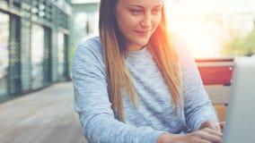 Ung och stilig kvinna med bärbar datorsammanträde i gatakafé och att bläddra rengöringsduken och social nätverksmatning som prata royaltyfri foto