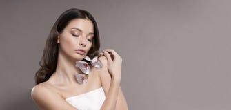 Ung och sund kvinna med den hållande orkidéblomman för ljust smink Beige bakgrund Fotografering för Bildbyråer
