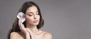 Ung och sund kvinna med ljust smink och orkidéblomma i hennes hår arkivbild