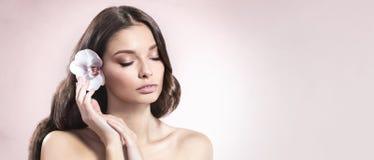 Ung och sund kvinna med ljust smink och orkidéblomma i hennes hår på ljus - rosa bakgrund Arkivbilder