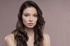 Ung och sund kvinna med ljust smink på beige bakgrund arkivfoto